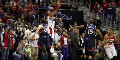 Paul Pierce shoots a three-point basket while being defender by Kyle Korver (Photo by Alex Brandon/AP)