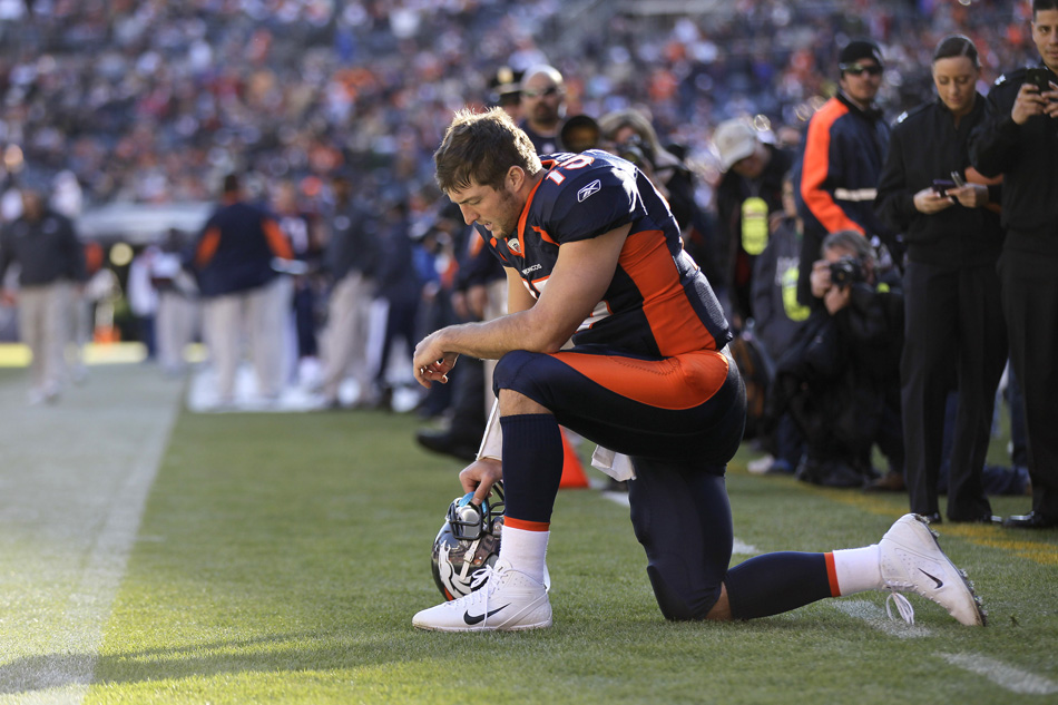 Tim Tebow prays before a game in 2011 when he was with the Denver Broncos (Julie Jacobson/AP).
